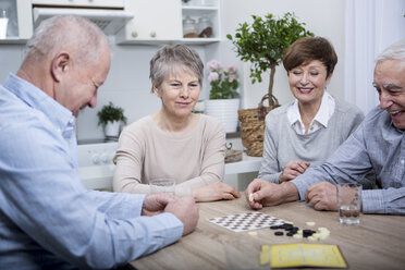 Group of seniors having a games evening at home - WESTF23367