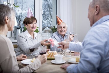 Two senior couples celebrating birthday party, toasting with red wine - WESTF23379