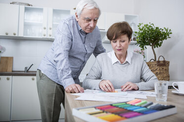 senior woman painting with crayons, husband watching - WESTF23394