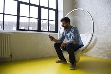 Smiling man sitting on swing in his loft looking at cell phone - ABZF02039
