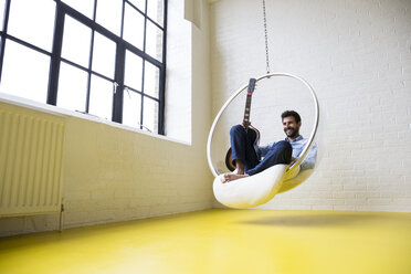 Smiling man with guitar sitting on swing in his loft - ABZF02048