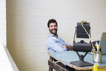 Portrait of smiling man relaxing at desk in his loft - ABZF02060