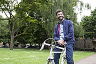 Smiling young man with bicycle in a park - ABZF02075