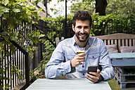 Portrait of smiling young man with cell phone and glass of beer relaxing in garden - ABZF02078