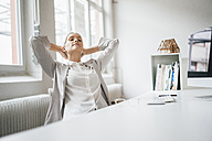Businesswoman relaxing at desk in her office - JOSF01061