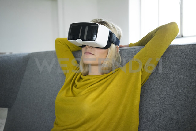 Woman sitting on couch wearing virtual reality glasses - JOSF01070 - Joseffson/Westend61