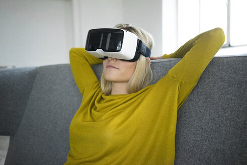 Woman sitting on couch wearing virtual reality glasses - JOSF01070