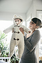 Mother holding up baby in a polar bear costume - MFF03597