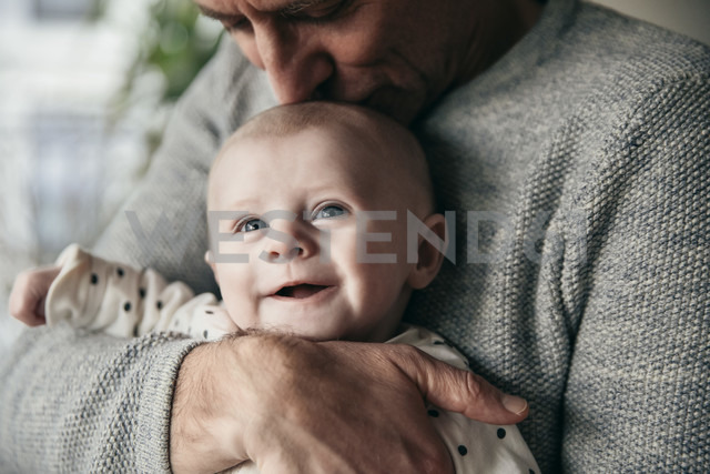 Mature father kissing laughing baby on its head - MFF03600