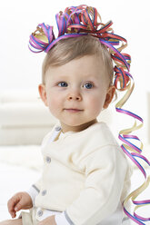 Portrait of ssmiling toddler with streamer on his head - FSF00933