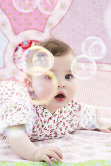 Portrait of astonished baby girl watching soap bubbles - FSF00939