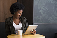Laughing young woman sitting in a coffee shop looking at tablet - ABZF02083