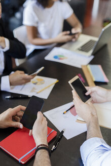 Business people using cell phones during a meeting in office - GIOF02653