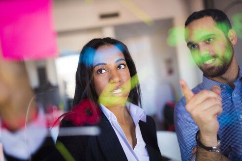 Businessman and businesswoman brainstorming in office - GIOF02689