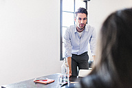 Businessman looking at colleague in office - GIOF02692
