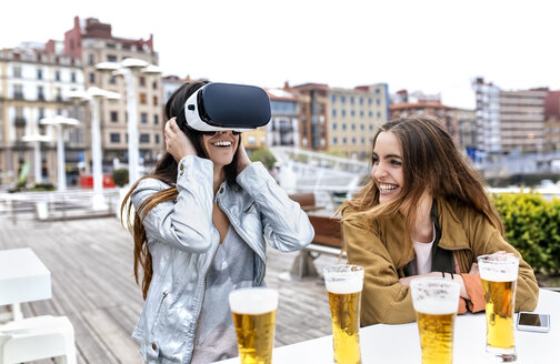 Two young women having fun with VR glasses in the city - MGOF03421
