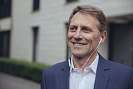 Portrait of smiling mature businessman outdoors with earphones - MFF03610