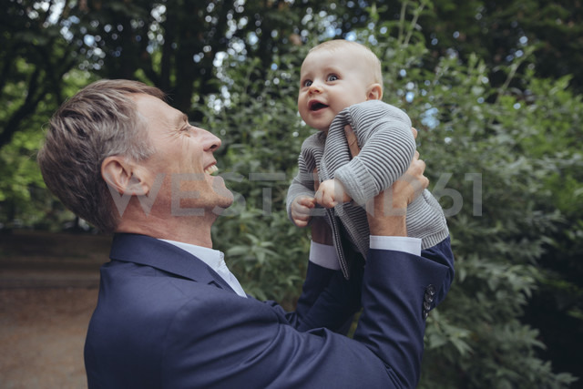 Happy mature businessman holding up baby boy outdoors - MFF03613
