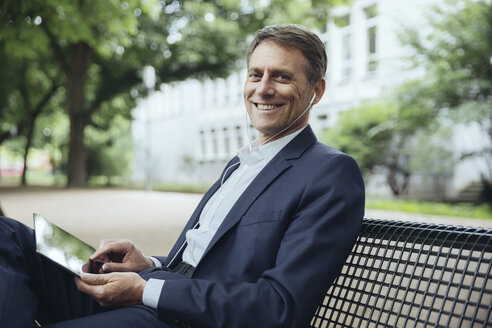 Smiling mature businessman sitting on park bench with tablet and earphones - MFF03616