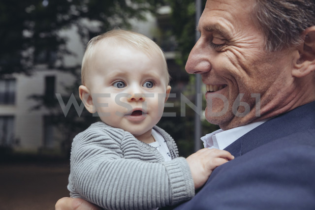 Happy mature businessman holding baby boy outdoors - MFF03619