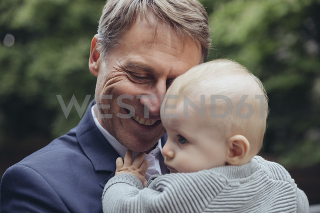 Happy mature businessman holding baby boy outdoors - MFF03622