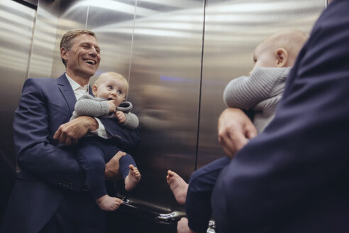 Happy mature businessman holding baby boy looking in mirror in elevator - MFF03625