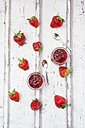 Two glasses of homemade strawberry jam, tea spoons and strawberries on white wood - LVF06151