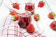 Glass of homemade strawberry jam, kitchen towel and strawberries on white wood - LVF06154