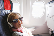 Portrait of smiling little girl with headphones sitting on an airplane - FKF02332