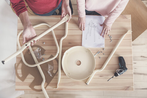Young couple assembling flat-pack stool at home, partial view - RTBF00888