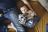 Baby boy lying on couch besides his father using smartphone - MFF03629
