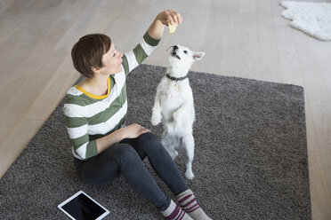 Woman sitting on the floor in the living room with her dog - RBF05669