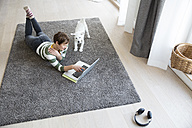 Woman lying on the floor in the living room using laptop while dog watching her - RBF05672