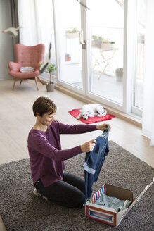 Smiling woman at home unpacking parcel with garment - RBF05675