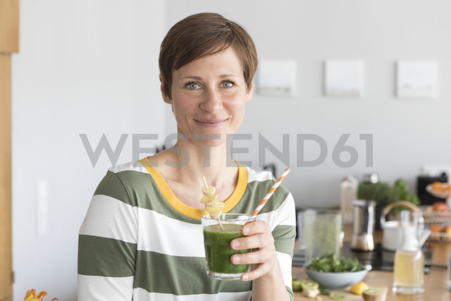 Portrait of smiling woman with green smoothie in the kitchen - RBF05681