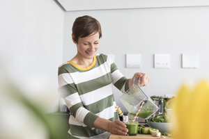 Smiling woman pouring green smoothie into a glass - RBF05684