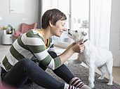 Smiling woman sitting on the floor in the living room cuddling with her dog - RBF05696