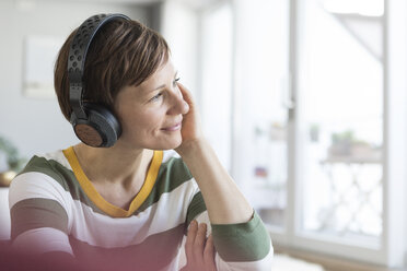 Smiling woman listeningmusic with headphones at home - RBF05699