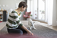 Smiling woman sitting on the floor at home playing with her dog - RBF05705