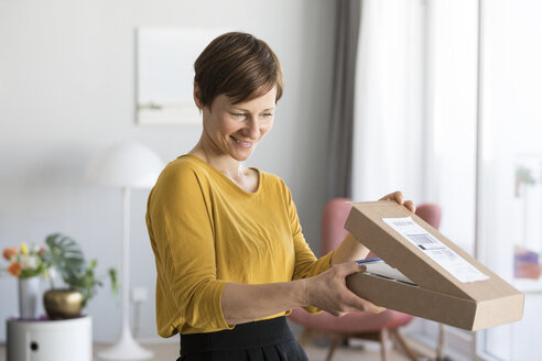 Smiling woman unpacking parcel at home - RBF05717