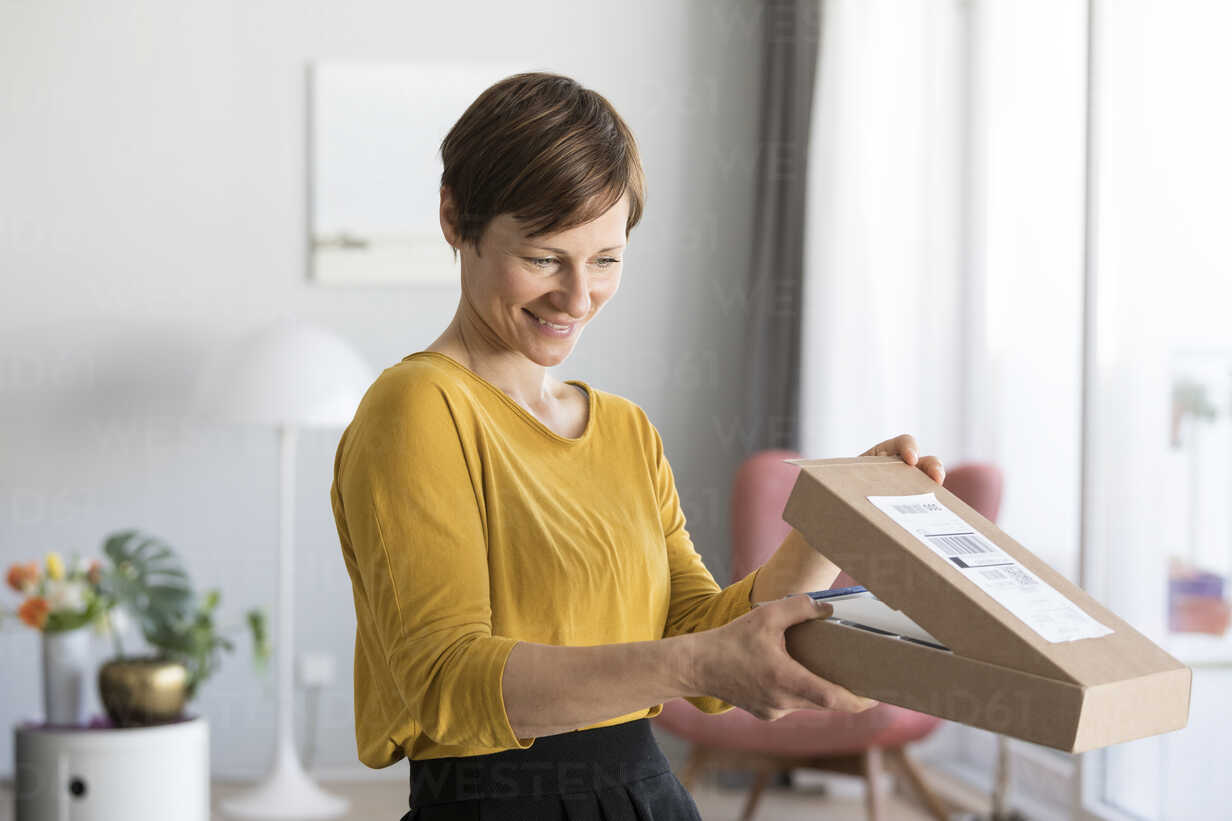 Smiling woman unpacking parcel at home - RBF05717 - Rainer Berg/Westend61