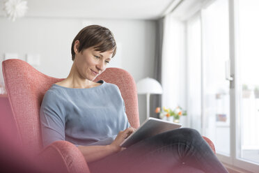 Portrait of woman sitting on armchair at home using tablet - RBF05720