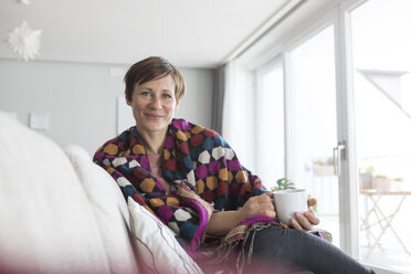 Portrait of smiling woman relaxing with cup of coffee on the couch - RBF05732