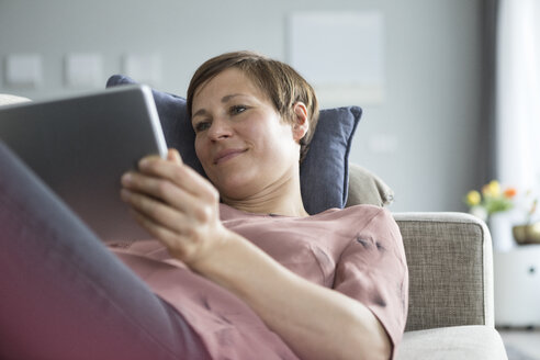 Portrait of smiling woman lying on the couch using tablet - RBF05738
