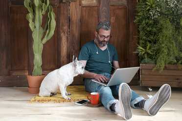 Bearded man sitting with his dog on the floor at home using laptop - RTBF00896