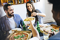 Happy friends having French fries and pizza at home - GIOF02751
