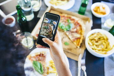 Hand taking cell phone picture of pizza on table - GIOF02754