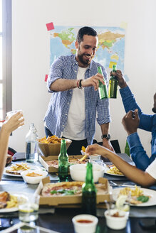 Group of friends clinking beer bottles at dining table - GIOF02769