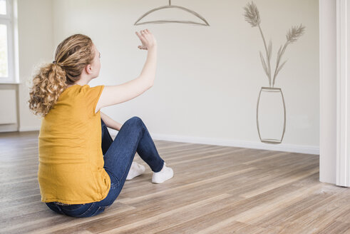 Young woman in new home sitting on floor thinking about interior design - UUF10812