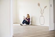 Young woman in new home sitting on floor using tablet - UUF10815
